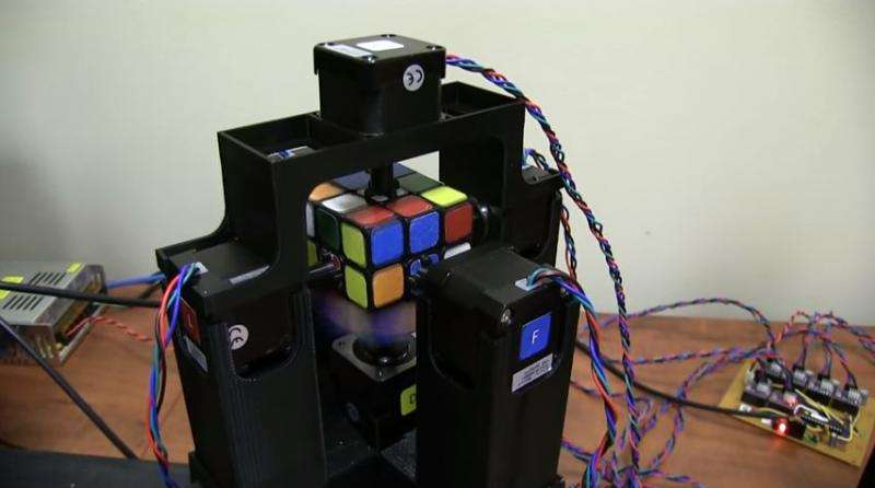 Record-seeking pair show off robot solving Rubik's Cube