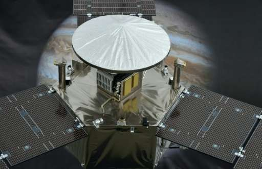 A 1/4 scale model of NASA's Juno spacecraft pictured in front of an image of Jupiter at the Jet Propulsion Laboratory (JPL) in P