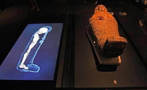 A 3D image of a CT scan of an Egyptian mummy is projected next to its sarcophagus