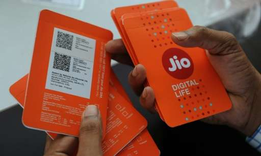 A customer in Mumbai selects a Reliance Jio Infocomm 4G mobile simcard offering an audacious free service for the rest of 2016