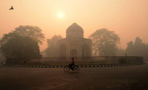 A cyclist rides along a street as smog envelops a monument in New Delhi on October 31, 2016, a day after the Diwali festival