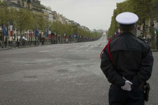A French policeman stands guard at the top of the empty Champs-Elysees in Paris on April 25, 2016
