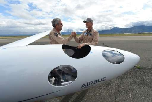 Airbus Group CEO Tom Enders (R) shakes hands with chief pilot Jim Payne after the two landed a test flight of the Airbus Perlan