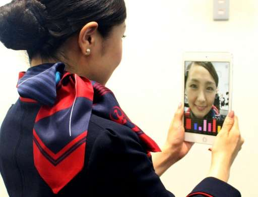A Japan Airlines flight attendant checking her smile using a Shiseido app