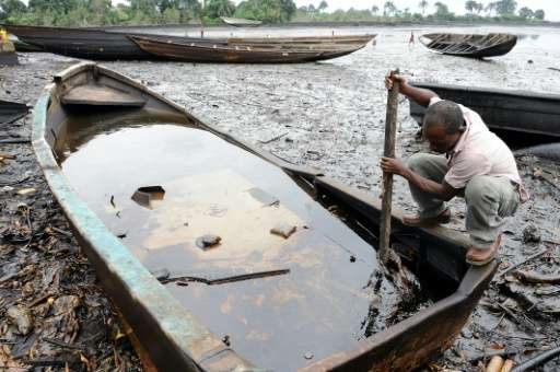 A man in Nigeria's Ogoniland region looks at a mix of oil and water in a boat on the Bodo waterways, heavily polluted by oil spi