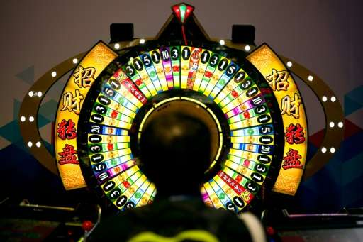 A man tries his luck at a wheel of fortune machine at the Global Gaming Expo Asia held in Macau on May 17, 2016