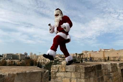 A man wearing a Santa Claus costume walks atop Jerusalem's Old City walls on December 23, 2016