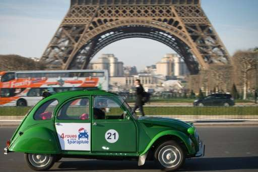 An employee of the French tourist company Four Wheels Under an Umbrella drives a Citroen 2CV electric car close to the Eiffel to
