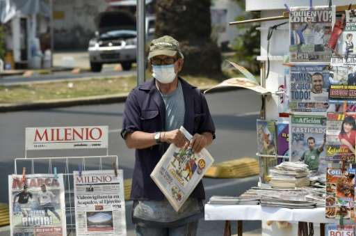 A newspaper vendor wears a surgical mask in smog-covered Mexico City on May 3, 2016