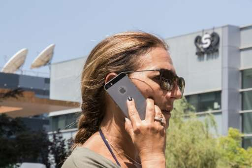 An Israeli woman uses her iPhone in front of the building housing the Israeli NSO group, on August 28, 2016, in Herzliya, near T