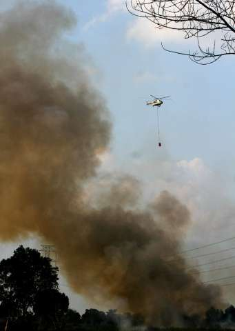 An Mi-17 helicopter from Indonesia's National Disaster Mitigation Agency conducting water-bombing operations to put out forest f