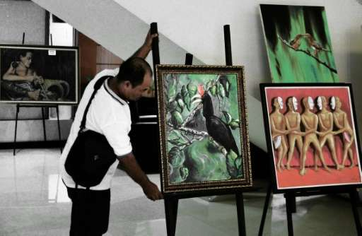 A painter arranges a painting of a rare hornbill species during an exhibition in Pontianak, West Kalimantan province