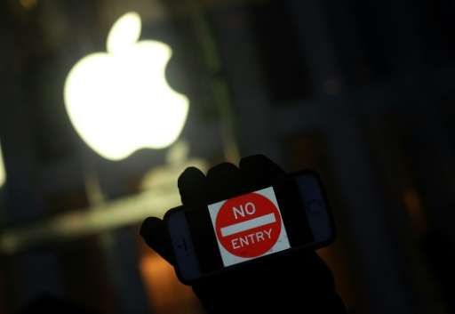 "A protester holds up his iPhone with a sign ""No Entry"" during a demonstration in New York on February 23, 2016, Apple"
