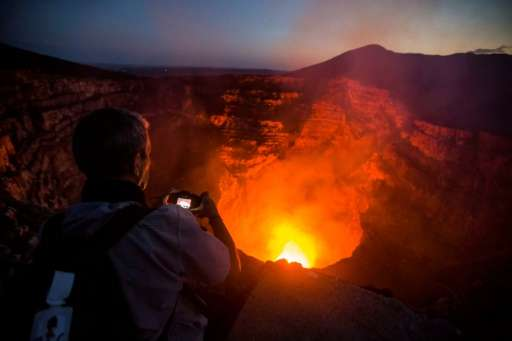A tourist takes pictures of a lava lake inside the crater of the Masaya Volcano in Nicaragua