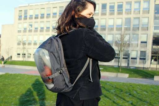 "A woman wears ""The Plant Bag"", a backpack fitted with a breathing mask connected to the pack which contains a plant on"