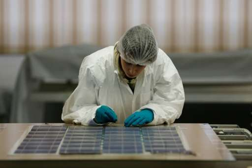 A woman works on a solar panel at the SNA factory in Tourouvre