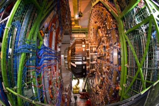 A worker stands below the Compact Muon Solenoid of the Large Hadron Collider during maintenance on July 19, 2013 in Meyrin, Swit