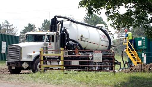 A worker unloads oil that has been removed from the Kalamazoo River after a 30 inch-wide underground pipeline owned by Calgary,