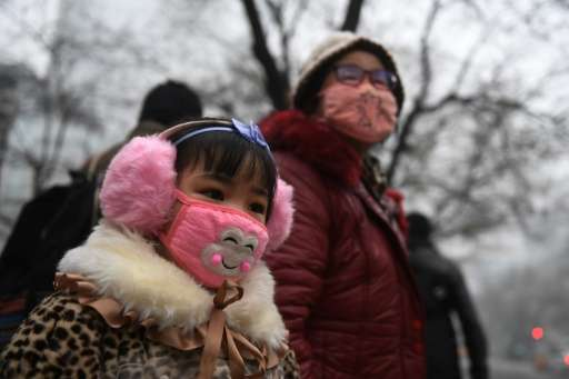 A young girl waits to cross a road in Shijiazhuang on December 21, 2016