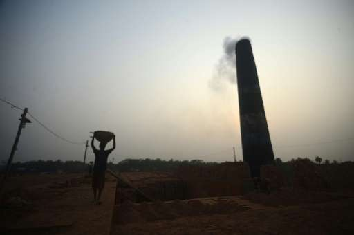 Bangladeshi labourers work at a brick factory on the outskirts of Khulna on January 19, 2016