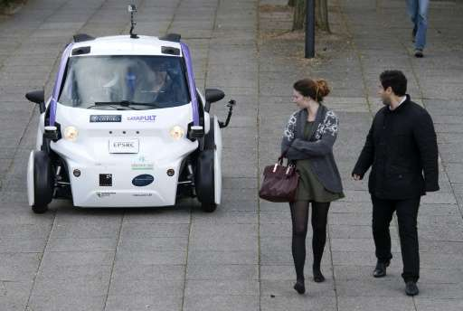 Bystanders look at an autonomous self-driving vehicle as it is tested in a pedestrianised zone during a media event in Milton Ke
