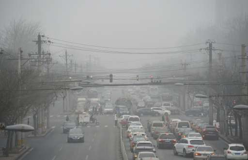 Cars drive below a blanket of smog on a heavily polluted day in Beijing on December 26, 2015