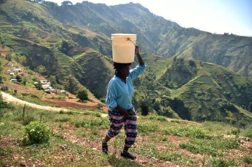 Cathy walks home with a bucket of water on her head in Godet, in the commune of Kenskoff, near the Haitian capital, Port-au-Prin