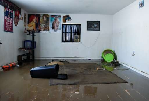 Debris and water covers a floor in the home of Debbie and Benton Kelly in Pacific, Missouri on January 1, 2016
