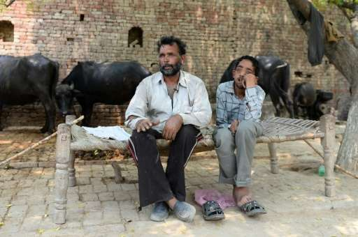 Dharam Veer (L) sits with his disabled son Vineet on a charpoy in the village of Gangnauli, in India's northern state of Uttar P