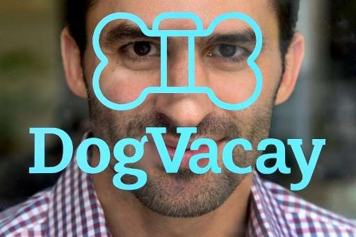 DogVacay co-founder and CEO Aaron Hirschorn poses behind the company's logo on the entrance to company offices in Santa Monica,