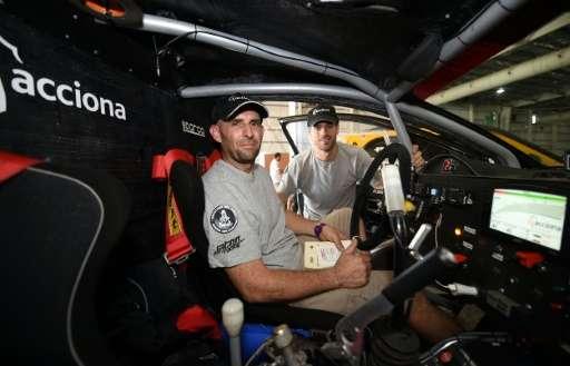 Driver Ariel Jatton (L) and co-driver Gaston Daniel Scazzuso of Argentina pose inside their Acciona Eco Power ahead of the 2016