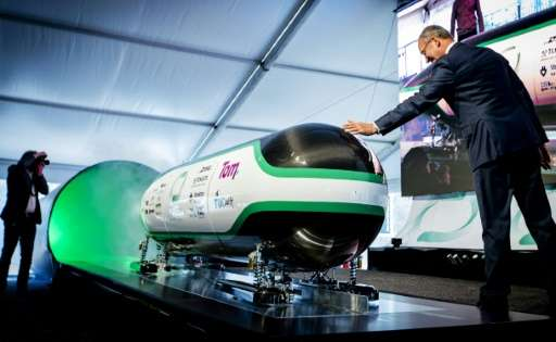 Dutch Minister for economic affairs Henk Kamp checks out the prototype during the unveiling of the Hyper Loop capsule from the D