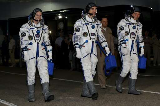 First-time astronauts Kathleen Rubins of NASA (L) and Takuya Onishi of the Japanese space agency (R) set off for a four-month mi
