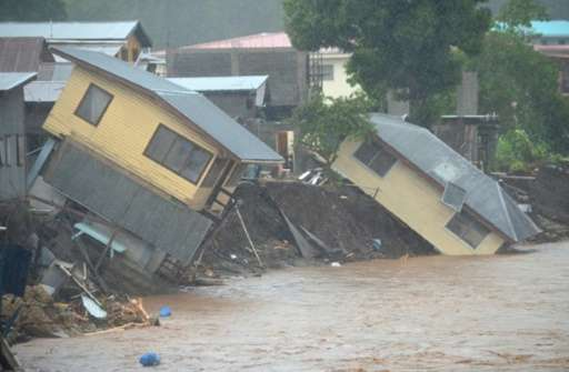 Flood waters run past damaged homes in the Solomon Islands' capital Honiara on April 4, 2014