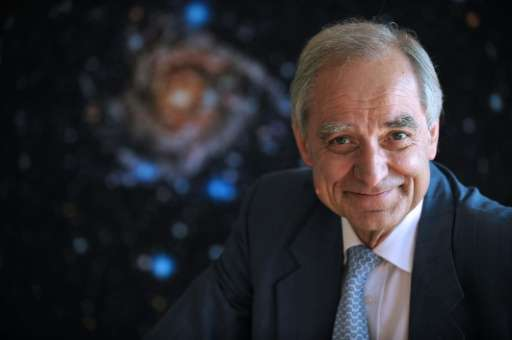 French astrophysician Andre Brahic poses in front of a picture of the IC 342 galaxy at the headquarters of the French Atomic ene