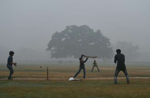 Indian teenagers play cricket in a park as heavy smog covers New Delhi, on November 7, 2016