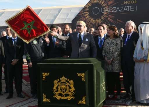 Moroccan King Mohammed VI (C) waves the Moroccan flag as he inaugurates the Noor 1 Concentrated Solar Power plant, some 20 kilom