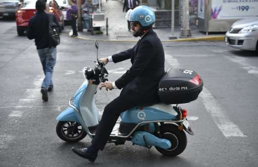 "One of the electric motorcycles from the ""Econduce"" (Edrive) program takes to the roads of Mexico City, a sprawling me"