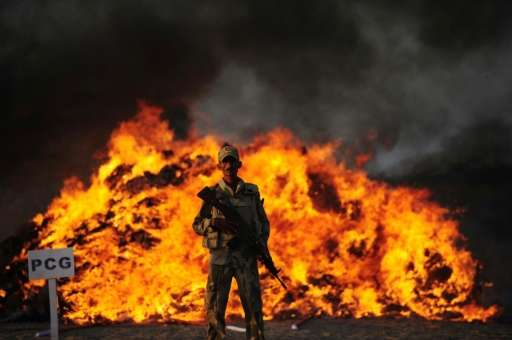 Pakistani police burn seized illegal drugs on the outskirts of Karachi on October 15, 2015