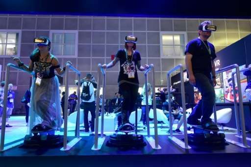 People 'skateboard' while sampling Samsung's Gear VR headsets powered by Oculus at the Los Angeles Convention Center during the