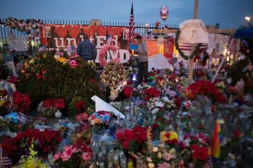 People visit a makeshift memorial near the Inland Regional Center in San Bernardino, California where Syed Farook and Tashfeen M