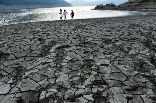 People walk along a dried and cracked river beach of the Yangtze River in China