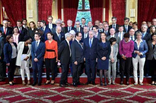 President Francois Hollande (centre) and his cabinet pose for a group photo after France became the first country to ratify the