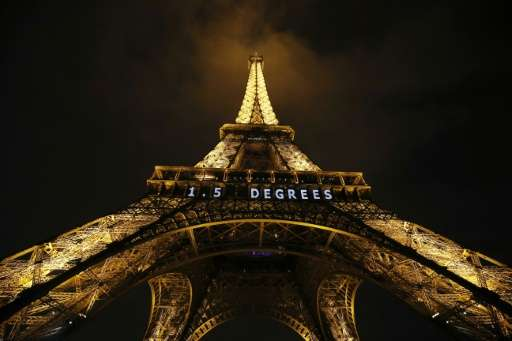 """1.5 Degrees"" in white neon is lit on the Eiffel Tower in the French capital during the COP21 United Nations Climate C"
