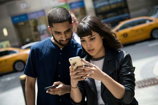 Sameer Uddin and Michelle Macias play Pokemon Go on their smartphones, outside Nintendo's flagship store in New York, on July 11