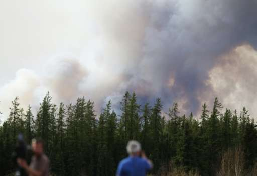 Smoke rises off Highway 63 on May 7, 2016 outside Fort McMurray, where raging forest fires have forced more than 88,000 from the