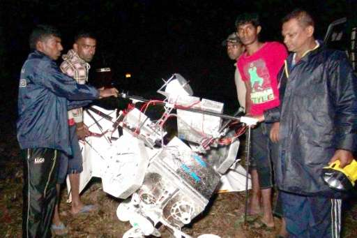 Sri Lankan men at a tea plantation look at the wreckage of a Google balloon that crashed in the central part of the country in G