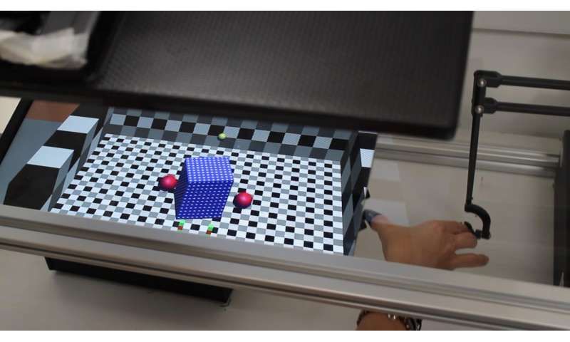 Subject manipulating a cube with hand (right) in a virtual relaity game.