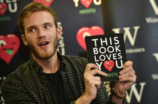 Swedish video game commentator Felix Kjellberg, aka PewDiePie poses with his new book, 'This book loves you' at an event in cent