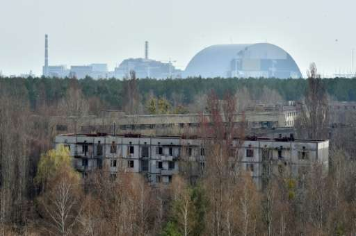 The Chernobyl nuclear power plant is seen in the distance from the ghost city of Prypyat on April 8, 2016